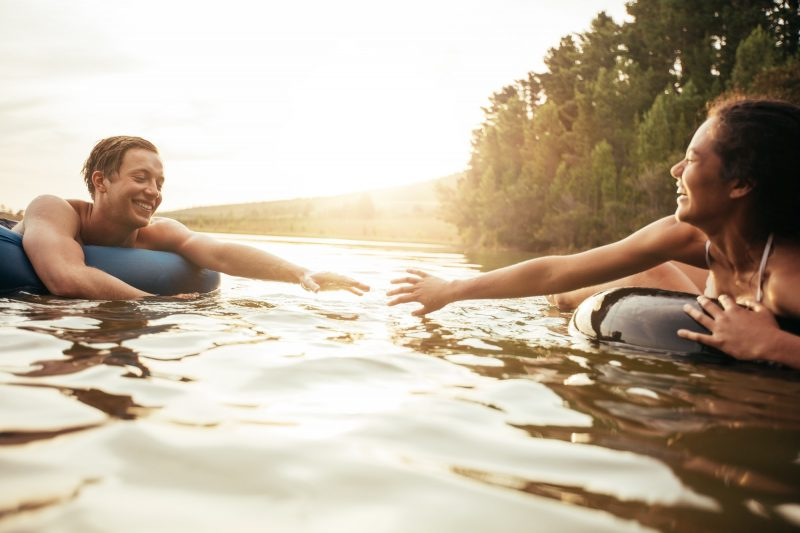 Young couple floating on inner tubes in lake