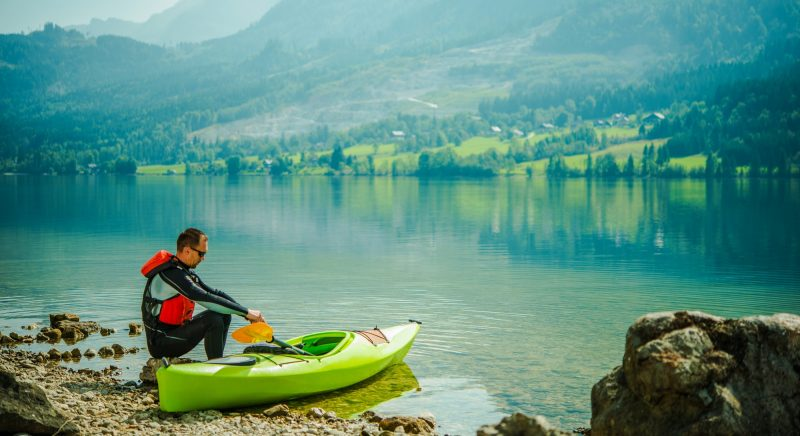 Man Relaxing By Lake After Long Day Of Canoeing.